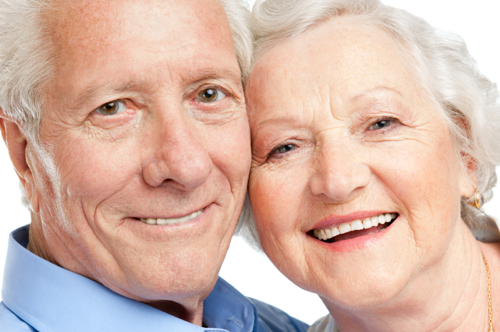 Two no-slip-denture smiles thanks to your implant dentist for Manhattan